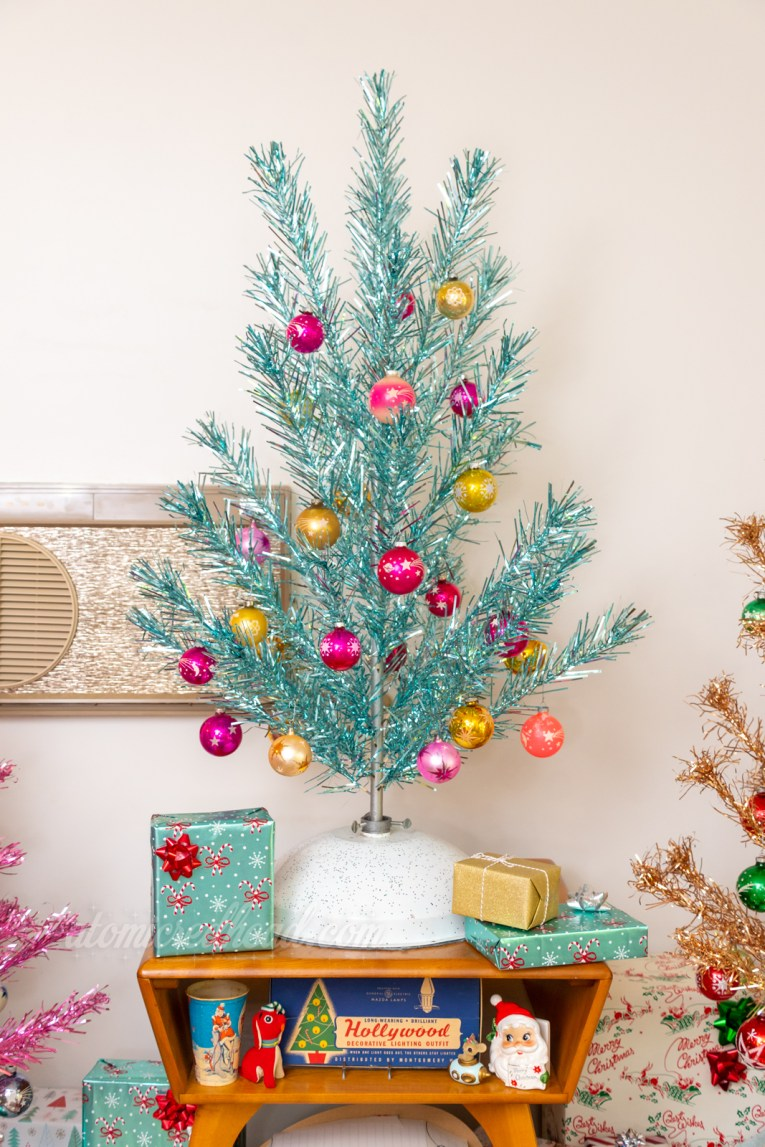 """Our blue aluminum tree sits atop a small table. Also on the table is a box of vintage Christmas lights reading """"Hollywood"""""""
