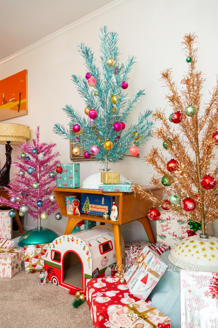 A trio of three foot aluminum trees, one pink, one blue, and one gold.