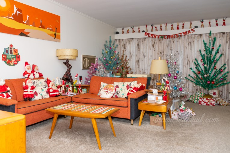 Looking into our living room. A couch set forms an L shape around a coffee table. Various plush Santas sit on the couches. Beyond them is the aluminum forest.