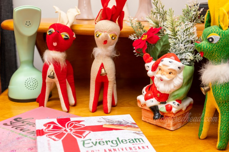 Three small stuffed reindeer, one red, one white, and one green, sit next to a ceramic planter of Santa stepping into a chimney.