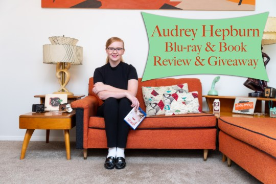"Myself, sitting on the couch, wearing a short sleeve black mock-turtle neck, and black pants, holding the Blu-ray of Audrey: More than an Icon. Text overlay reads ""Audrey Hepburn Blu-ray & Book Review & Giveaway"""