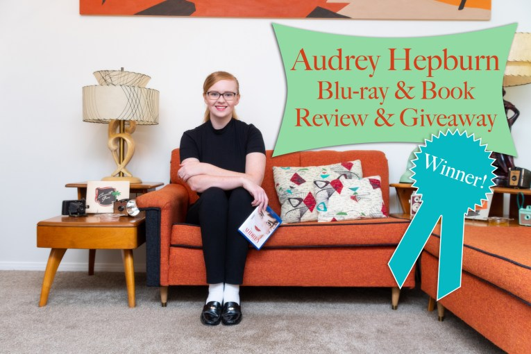 "Myself, sitting on the couch, wearing a short sleeve black mock-turtle neck, and black pants, holding the Blu-ray of Audrey: More than an Icon. Text overlay reads ""Audrey Hepburn Blu-ray & Book Review & Giveaway Winner"""
