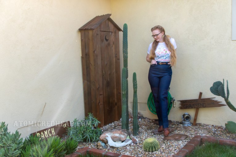 Myself standing in front of a western style outhouse with cacti in front, wearing a Cerro Gordo tee and western style jeans.