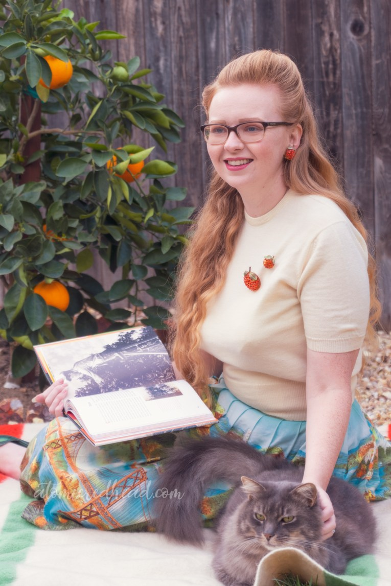 Sitting on a blanket in front of my orange tree, wearing a white sweater, with two orange brooches, and a skirt featuring various California landmarks, while reading and petting my cat.