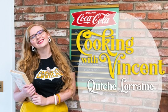 "Myself standing against a brick wall, wearing a black shirt with a bat shape with text reading ""Egghead"" and overlay text reading ""Cooking Vincent Quiche Lorraine"""