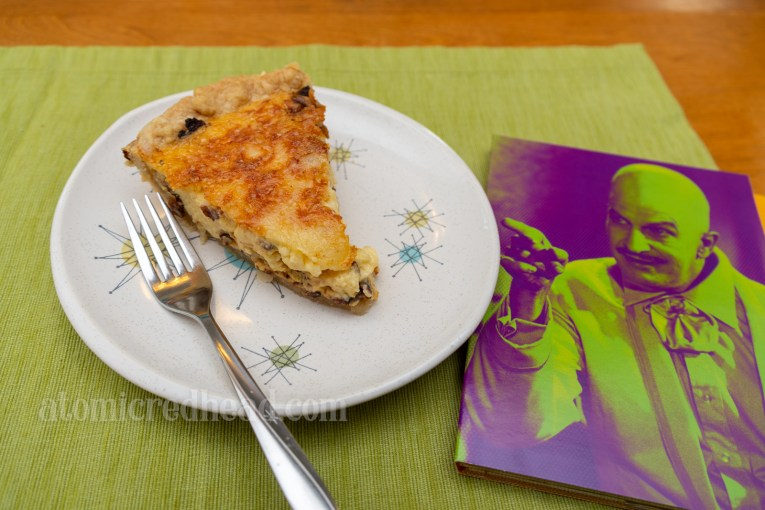Slice of quiche on a plate with a case from the Batman Blu-ray set featuring Egghead placed next to it.