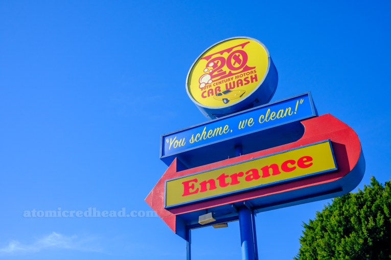 "A large, red, blue, and yellow sign reading ""20th Century Motors Car Wash 'You Scheme, We Clean,' Entrance"" With the ""Entrance"" in a red arrow."