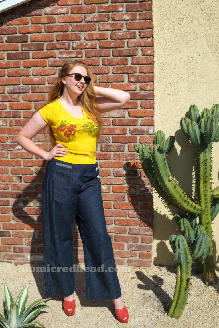 Myself, wearing a yellow terrycloth shirt featuring red hibiscus flowers and a parrot, blue wide leg jeans, red platform shoes, standing outside against a brick wall.