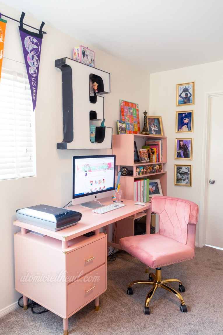 Overview of my corner. A computer sits atop a pink desk, with a pink velvet chair at it, behind it is a matching pink bookcase. A giant letter E hangs above the computer.
