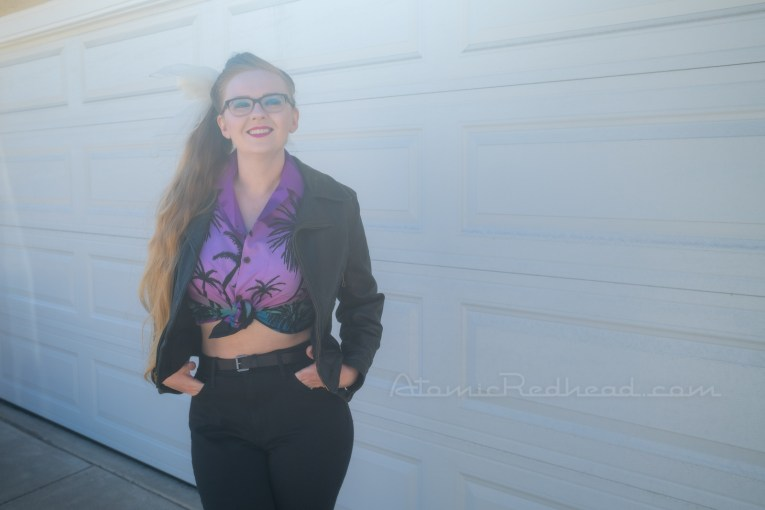 Myself standing in front of our garage door, wearing a black leather motorcycle jacket, purple and teal Hawaiian shirt, and black jeans.