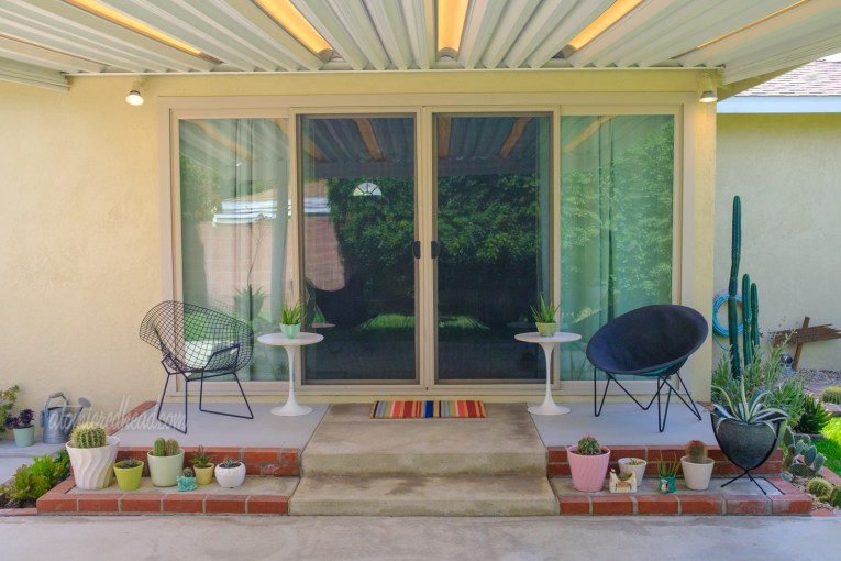 Our covered patio, looking toward the double sliding glass door. A wire diamond shape chair sits to the left, a circular chair with a black over sits on the right. Paired with each chair is a white Saarinen chair. Colorful pots full of cacti and succulents are around.
