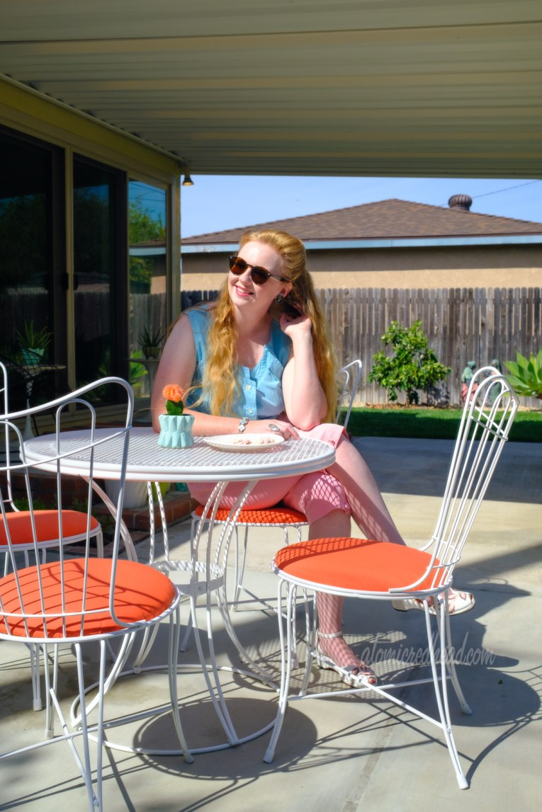 Myself, wearing a turquoise sleeveless top and pink peddle pushers, seated at a white metal table. A small cacti sits in a turquoise planter in the middle of the table, a plate with pink and white cookies sits nearby. The table is white with matching white chairs with orange cushions. In the background is the covered part of the patio with various chairs and plants.