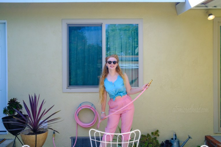 Myself, wearing a turquoise sleeveless top and pink peddle pushers, standing holding a pink garden hose.
