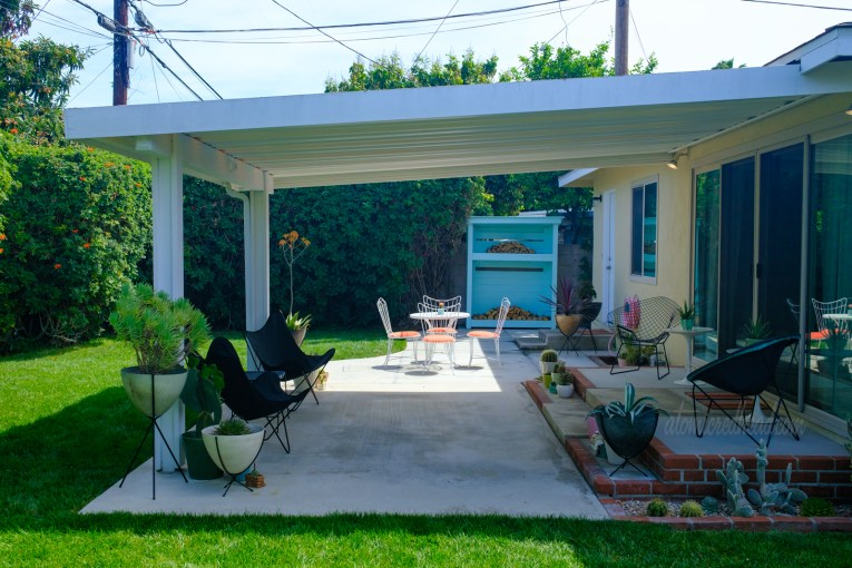 View of our covered patio toward the table, in the distance a turquoise wood shed sits against the fence.