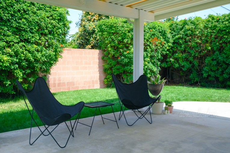 A pair of black butterfly chairs sit on the covered patio with a small black metal table between them.