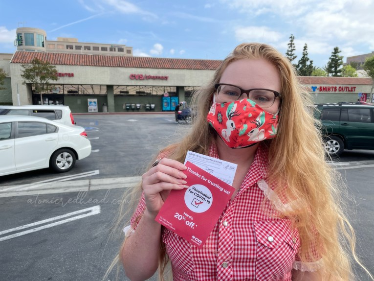 Myself holding my vaccine card, wearing a mask featuring jackalopes on it.