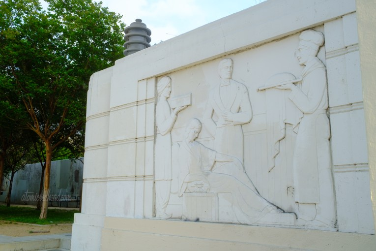 Carved into a small wall is an Art Deco image of a woman in bed being served by various men.