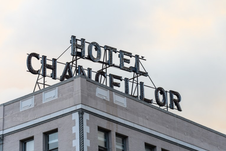 """Large letters spell out """"Hotel Chancellor"""" atop an apartment building."""