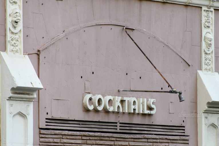 """The remains of an unknown bar, all that is left are small deco letters spelled out """"Cocktails"""""""