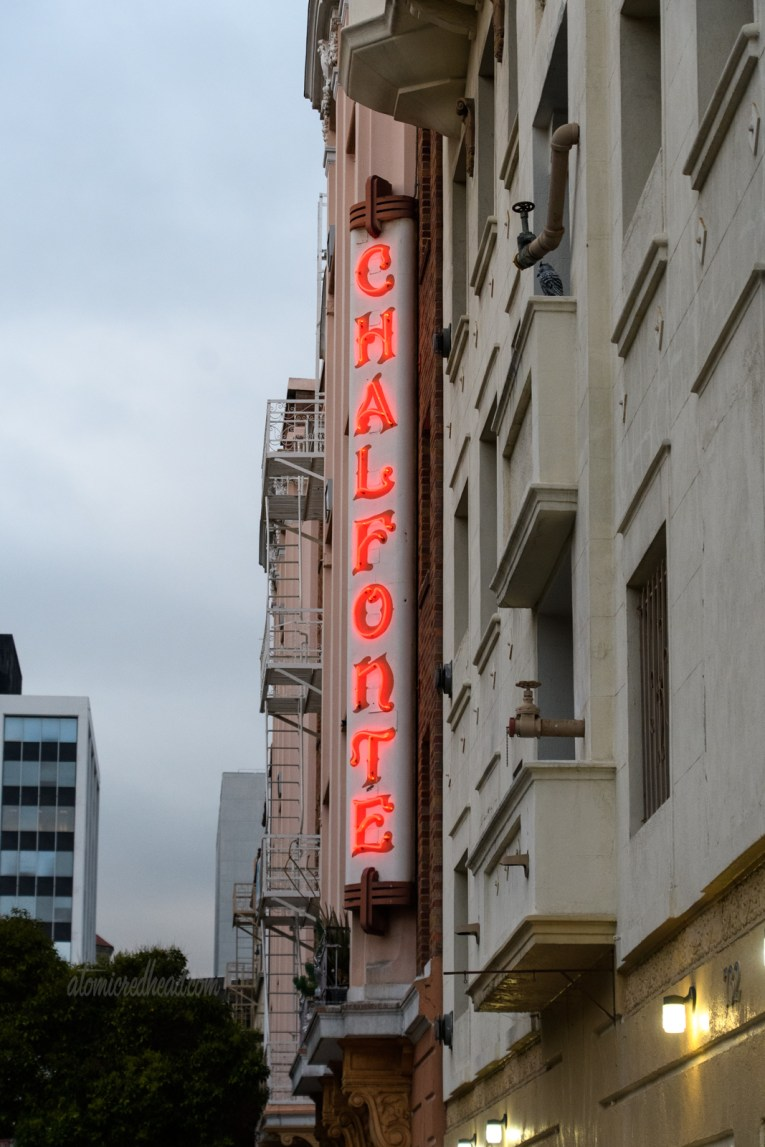 """A blade style neon sign juts from an apartment building reading """"Chalfonte"""" in red."""