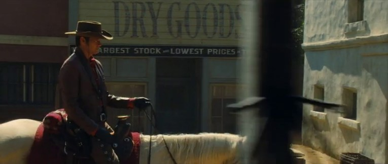 """Timothy Olyphant rides a horse into the scene, passing by a wooden store with """"Dry Goods"""" painted on the front."""