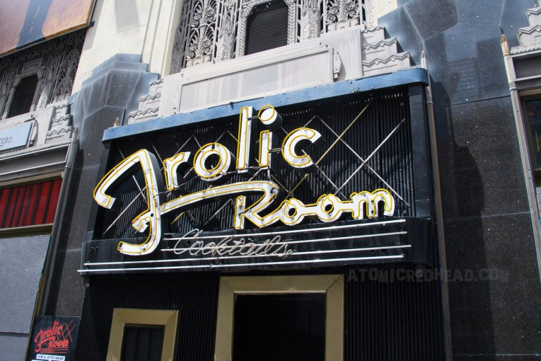 """In fanciful neon script it reads """"Frolic Room Cocktails"""" with art deco details flanking it."""