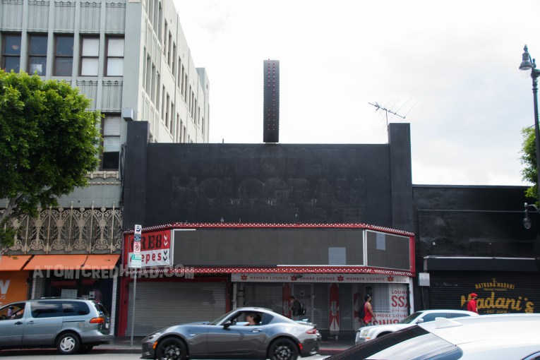 """A dilapidated theatre, with fading black paint. There are remnants of letters spelling out """"Hologram"""""""
