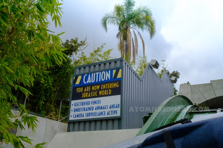 """Aboard a boat for the Jurassic World ride, a sign reads """"Caution You are now entering Jurassic World. Electrified Fences. Unrestrained Animals Ahead. Camera Surveillance Active."""