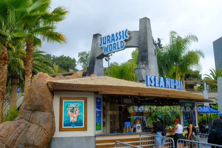 """The outdoor bar, Isla Nu-Bar, with the arch to the ride in the background. A poster on the bar features a tropical drink and text reading """"Taste Paradise"""""""