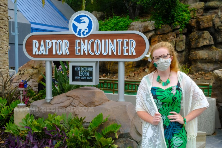 Myself standing in front of the Raptor Encounter sign, wearing a dress featuring a tropical leaf and frond design, with a necklace and bracelet that also features leaves and fronds, a white shawl is wrapped around my shoulders.
