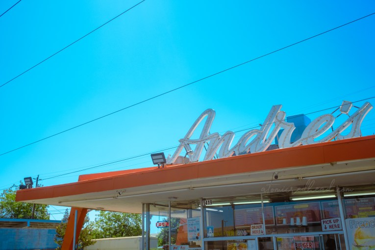 """Close-up of the Andre's sign which reads """"Andre's"""" in cursive across the top of the restaurant."""