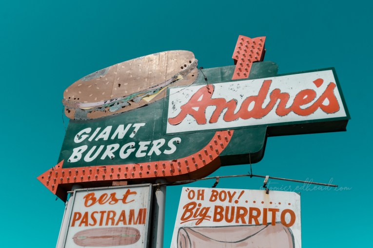 """Looking up at the Andre's sign. A large green sign reads """"Andre's Giant Burgers"""" and features a massive painted burger and an orange arrow. Other attached signs read """"Best pastrami in town"""" """"Oh Boy! Big Burrito"""""""