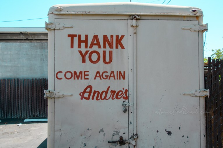 """A large metal crate painted white reads """"Thank you Come Again Andre's"""" in orange."""