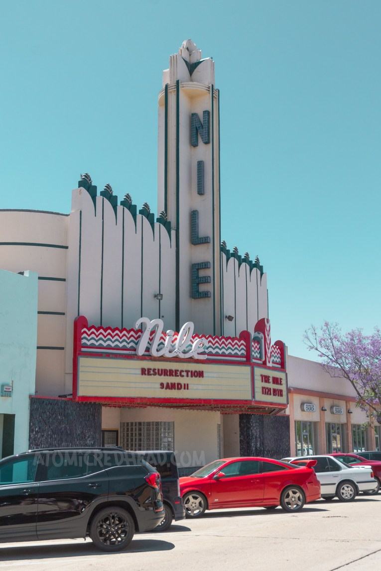 """The Nile Theater, an Art Deco style building with a tower in the center reading """"Nile"""" down it in blue letters. The marque features neon and reads """"Nile"""" in cursive white neon."""
