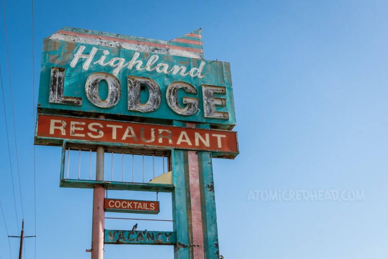 """Tall pink, red, and turquoise sign reading """"Highland Lodge Restaurant Cocktails"""" Various parts are faded and flaking. A portion below is missing."""