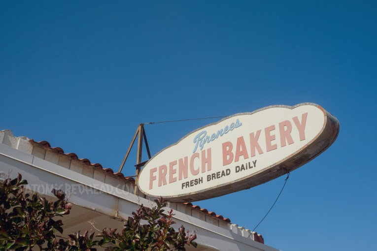 """Backlit plastic sign that is shaped like a loaf of French bread, with text reading """"Pyrenees French Bakery Fresh Bread Daily"""""""