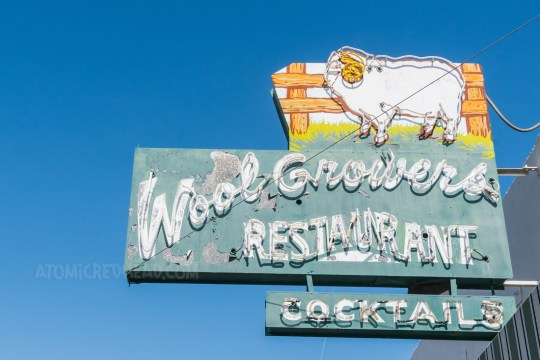 """A green neon sign reads """"Wool Growers Restaurant Cocktails"""" and features a sheet by a fence."""