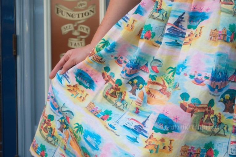 Close-up of the pattern on the dress, featuring icons such as the Matterhorn, Monorail, Sleeping Beauty Castle, colorful rock formations of the desert landscape of the Mine Train, the entrance to Adventureland, the entrance to Frontierland, the Mark Twain riverboat, Monstro the whale, the caterpillar vehicles of the Alice in Wonderland ride, and the western town of Rainbow Ridge.