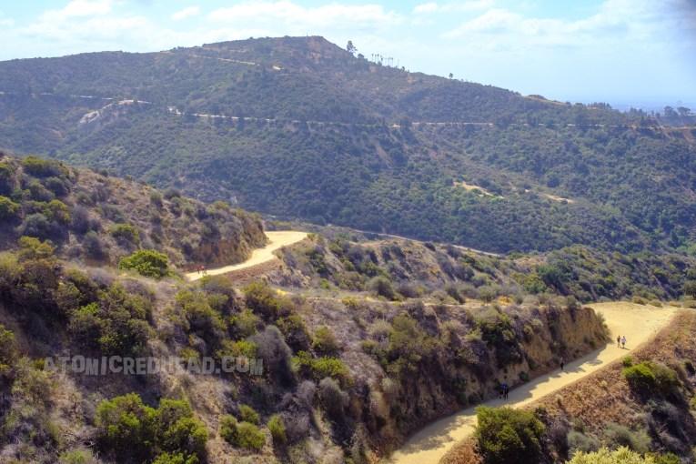 Green hills feature tan dirt pathways crisscrossing through the hills.