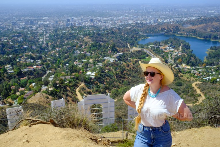Standing at the top, wearing a cowboy hat, white peasant blouse and blue jeans, the letters of the Hollywood sign behind me, and small houses of the hills past that, and then the streets of the city.