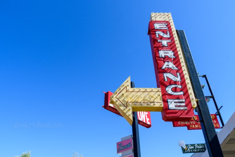 """A yellow and red neon sign with white letters reading """"entrance"""" and a yellow arrow pointing to the left."""