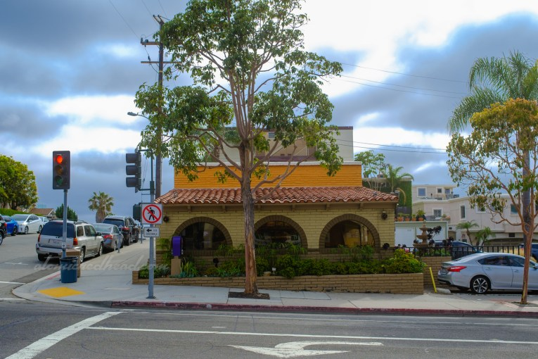 View of the Taco Bell, which is a brick structure painted in tan, brown, and orange.