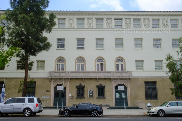 """A four story Spanish Colonial Revival building. An etched sign above the doors reads """"Young Mens Christian Association."""" Above the doors, one reads """"Mens Entrance"""" the other says """"Boys Entrance"""""""