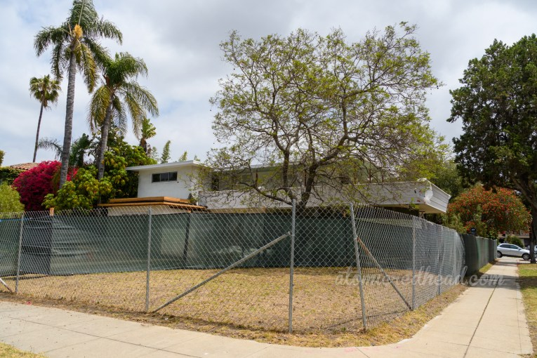 A mid-century modern home peeks out over a covered chain link fence.