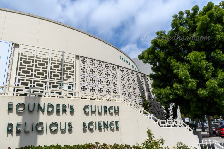 """A white circular building sits behind breeze blocks with cut outs of a cross in the middle. Green letters are mounted along the staircase reading """"Founders's Church Religious Science"""""""