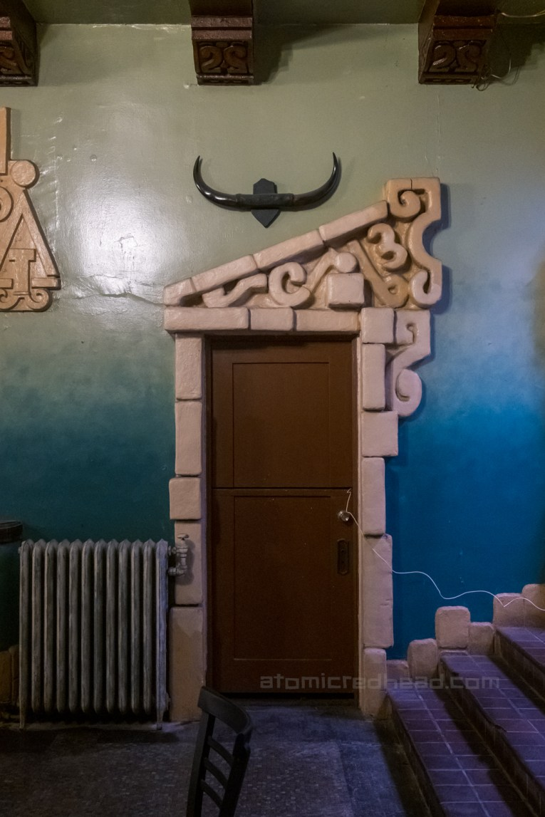 A doorway in the lobby which features an asymmetrical design above.