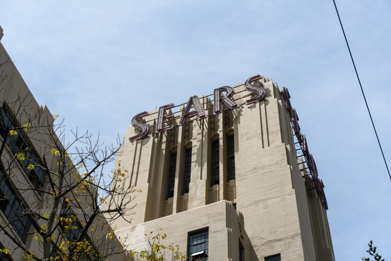 """Close-up of the tower at the very front of the building, with neon art deco style letters reading """"Sears"""""""