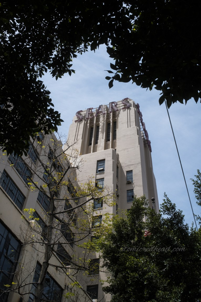 """The tower at the front, peeking through the leaves of a tree. Letters spelling """"Sears"""" is at the top."""