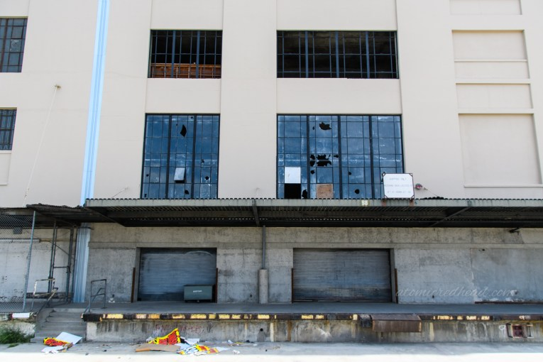 Loading bays near the back of the building. Litter from the closing sale scatters the ground.