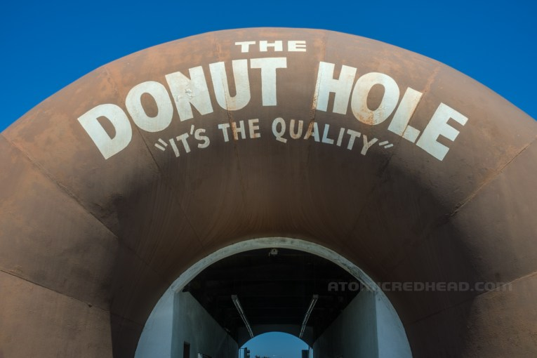 """Close-up of the text above the opening, reading """"The Donut Hole 'It's the Quality'"""" the opening to drive through is below."""